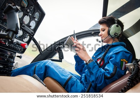 Young woman helicopter pilot reading map. - stock photo