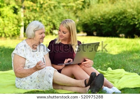 Young woman helping an elderly woman using the laptop in the park. MANY OTHER PHOTOS WITH THIS SENIOR MODEL IN MY PORTFOLIO.