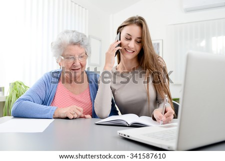 young woman helping an old senior woman doing paperwork and administrative procedures with laptop computer at home - stock photo