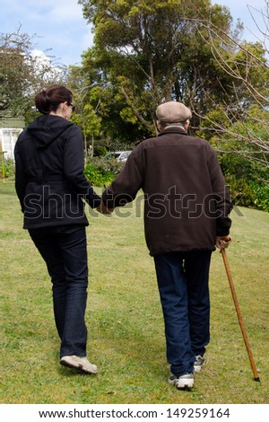 Young woman helping and supporting her grandfather to walk outdoor in the garden with his support walking stick. - stock photo