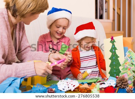 Young woman helping  girls to make decoration for Xmas  at home