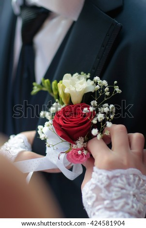 Young woman helping groom in black suit and tie with beautiful flower boutonniere of red rose before the ceremony