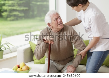 Young woman helping old man to stand up - stock photo