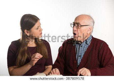 young woman helping senior man to pronounce sound and read book, man has dementia