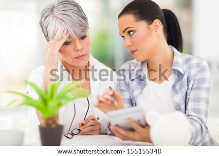 young woman helping senior mother sorting out her finances at home - stock photo