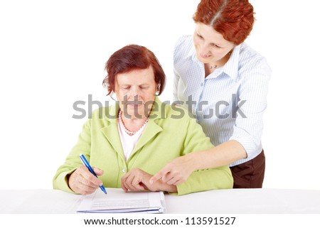 young woman helping senior woman to write a letter.