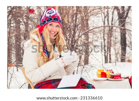 Young woman hid rug and reading book outdoors winter day. Beautiful blonde girl is drinking tea in winter. She is reading a book. Snow, frost, holiday, nature, park. New year. Drink coffee in winter. - stock photo