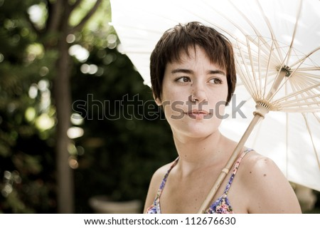 Young woman hides from sun under white umbrella - stock photo