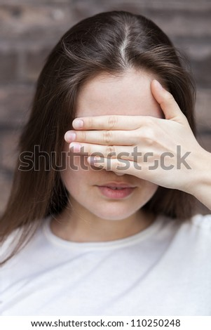 Young woman hides her face palm - stock photo