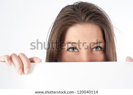Young woman hiding behind a billboard and looking on camera isolated on white background - stock photo