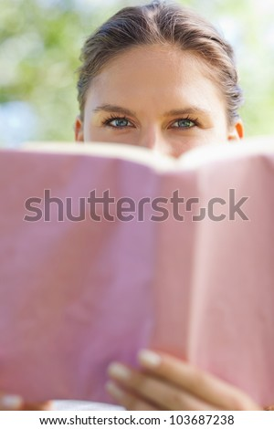 Young woman hiding her face behind a book in the park - stock photo
