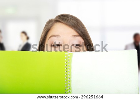 Young woman hiding her face behind a notebook. - stock photo