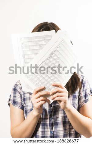 Young woman hiding her face behind sheets of paper