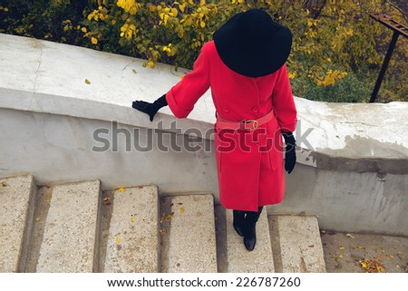 Young woman hiding her face under black hat, standing on the stairs. Autumn bushes background. Top view