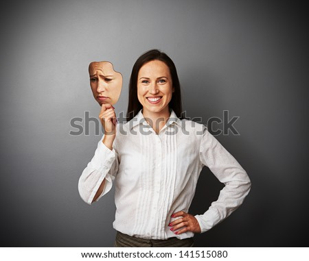 young woman hiding her good mood under sad mask - stock photo