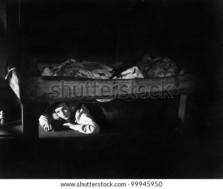 Young woman hiding under the bed - stock photo