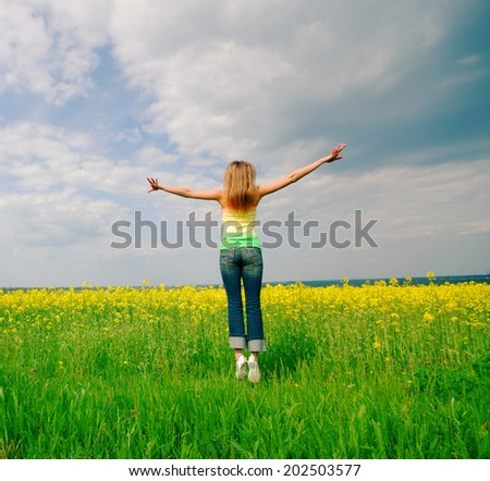 young woman highly has jumped up above  field,  bright sunny day