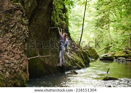 Young woman hiker climbing on safety cables in a gorge above the river - stock photo