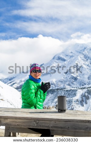 Young woman hiker drink coffee or tea in beautiful Himalaya mountains on hiking trip base camp Nepal. Active person resting outdoors in winter white nature. Female backpacker camping recreation active - stock photo