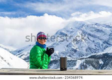 Young woman hiker drink coffee or tea in beautiful Himalaya mountains on hiking trip, Nepal. Active person resting outdoors in winter white nature using cup and thermos on wooden table in base camp. - stock photo