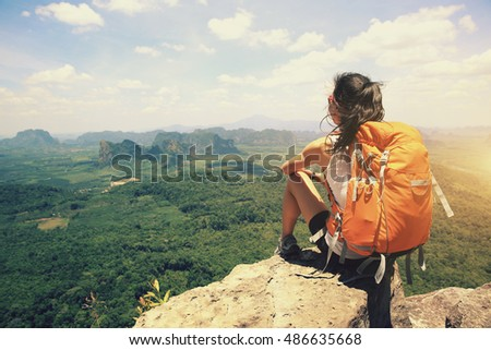 young woman hiker enjoy the view at seaside mountain peak