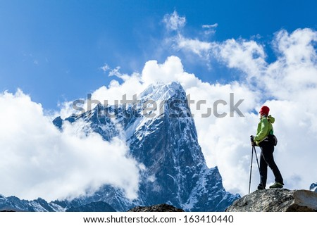 Young woman hiker hiking in Himalaya Mountains in Nepal. Trekking sport and fitness outdoors in high mountains Everest National Park Khumbu glacier.