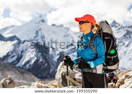 Young woman hiker hiking in Himalaya Mountains in Nepal. Trekking sport and fitness outdoors in high mountains Everest Nationa Park Khumbu glacier. - stock photo