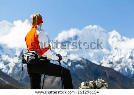 Young woman hiker hiking in Mount Everest National Park, Nepal. Himalayan nordic walking female looking at beautiful mountain view.