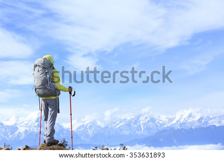 young woman hiker on beautiful rolling clouds mountain peak