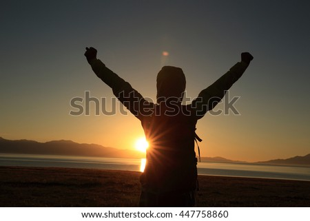 young woman hiker open arms under the sunrise at sea