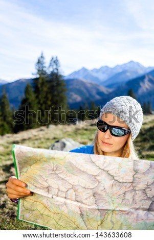Young woman hiker reading map in mountains on hiking trip. Female trekker camping and planning in autumn nature, outdoors activity, navigation and lost concept - stock photo
