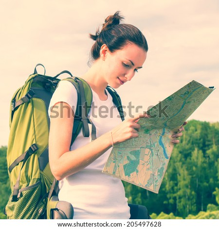 Young woman hiker reading map on hiking trip. Female trekker - stock photo