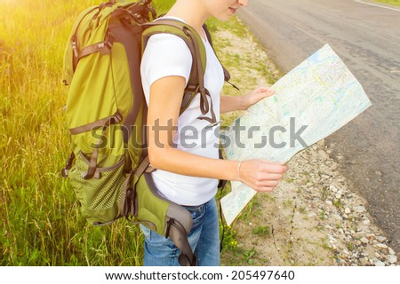 Young woman hiker reading map on hiking trip. Female trekker