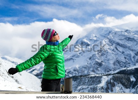 Young woman hiker resting and drinking coffee or tea in beautiful Himalaya mountains on hiking trip, Nepal. Female backpacker active person resting camping outdoors in base camp, winter white nature. - stock photo