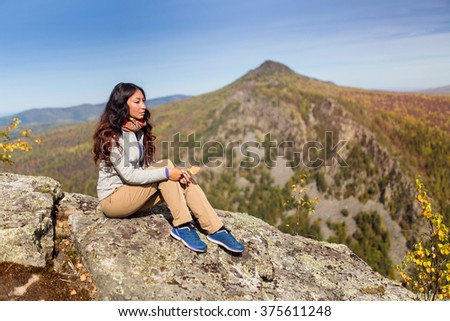 Young woman hiker sitting on cliff's edge and looking to a blue sky - stock photo