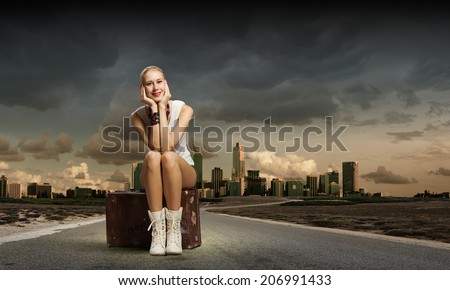 Young woman hiker sitting on suitcase along roadside