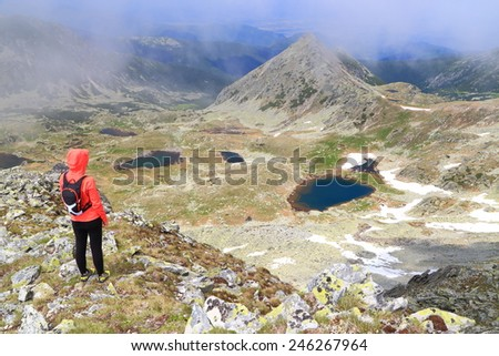 Young woman hiker standing above beautiful mountains and lakes in summer - stock photo