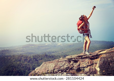 young woman hiker taking photo with smart phone at mountain peak - stock photo
