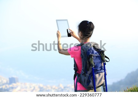 young woman hiker use digital tablet taking photo at mountain peak