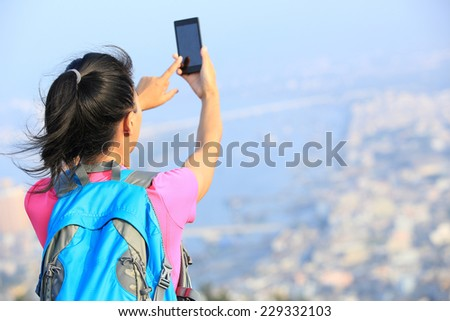 young woman hiker use smart phone taking photo at mountain peak