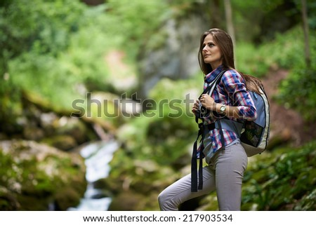 Young woman hiker with backpack crossing a river among boulders covered with moss in a canyon - stock photo