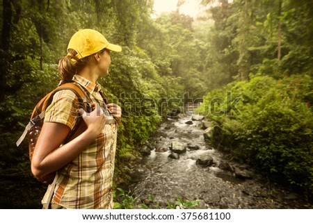 Young woman hiker with backpack standing and enjoying rain forest and river view.Lombok, Indonesia. Tourist hiking in the deep jungle - stock photo