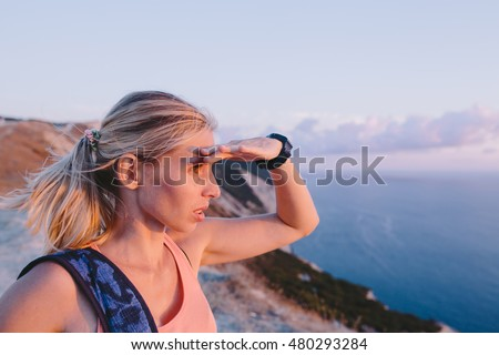Young woman hiker with backpack standing on mountain and looking forward with raised hand