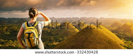 Young woman hiker with backpack standing on top of the mountain and enjoying great panoramic view on Chocolate Hills on the island of Bohol. Philippines.  - stock photo