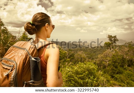 Young woman hiker with backpack standing on top of the mountain and enjoying  mountains view.Summer holiday concept - stock photo