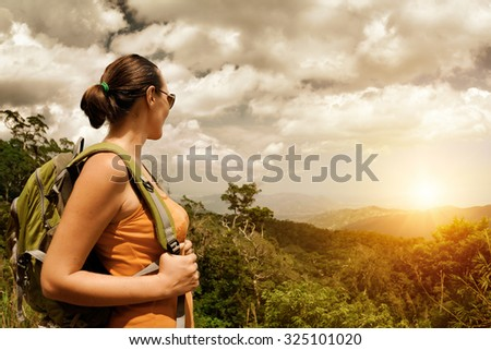 Young woman hiker with backpack standing on top of the mountain and enjoying  sunset view.Traveling along Asia, freedom and active lifestyle concept - stock photo
