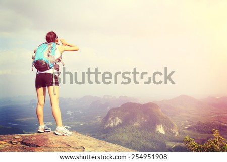 young woman hiker yelling at  mountain peak - stock photo