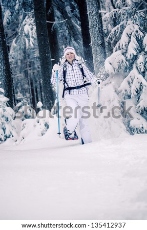 young woman hiking  in a snowy forest