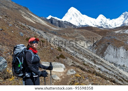 Young woman hiking in Himalaya Mountains, Nepal. Beautiful mountain landscape. Travel and trekking destination for tourists and trekkers - stock photo