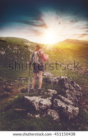 Young woman hiking in the alps at sunrise standing with her back to the camera on a rocky outcrop on a steep mountain slop - stock photo